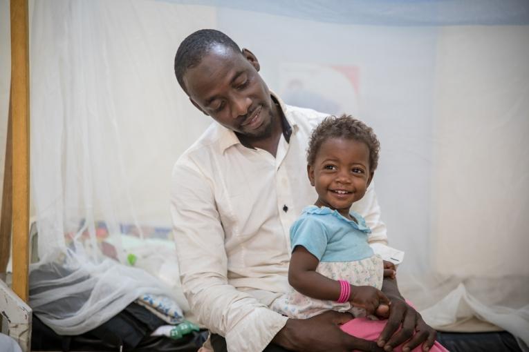 Mohammed Usseini et sa fille Oumi. Il y a plus d'un an, l'épouse de Mohammed a été blessée à l'épine dorsale, prise dans un feu croisé alors qu'elle tentait de fuir son village situé dans la zone rouge, au Nord-Est du Nigéria, pour chercher refuge au Cameroun.  © Pierre-Yves Bernard / MSF