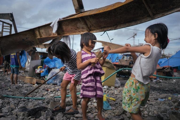 Des enfants jouent dans les décombres après la destruction de leur foyer par un incendie.  © Hannah Reyes Morales