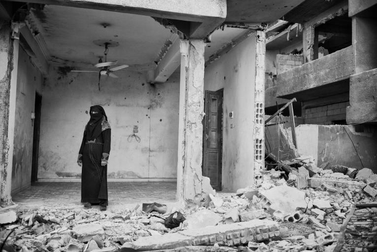 Une femme regarde ce qui a été un jour sa maison, en ruineaprès les offensives sur Rakka.  © Eddy Van Wessel