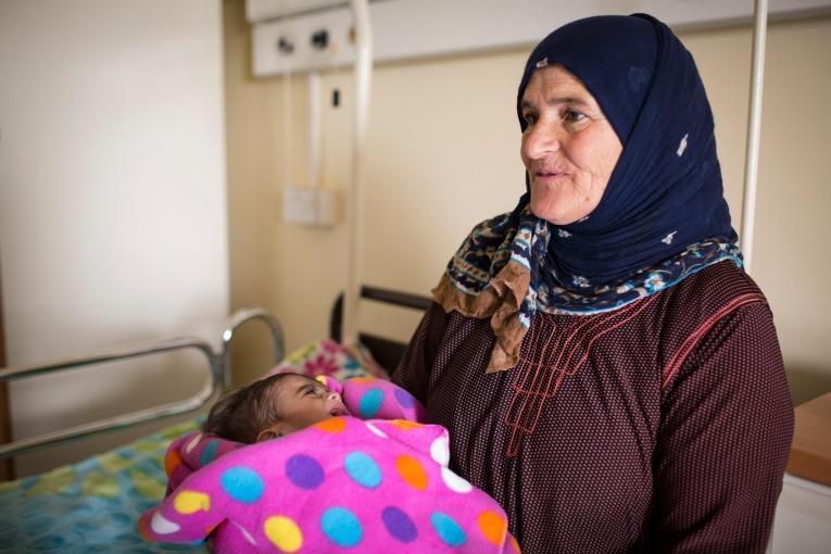 La famille du petit Mohamed, dans les bras de sa grand-mère, devait emprunter de l'argent auprès de sesproches pour pouvoir payer chaque visite à l'hôpital, jusqu'au jour où on leur a parlé d'un service de pédiatrie géré par MSF qui fournissait des services de santé gratuits.  © Florian SERIEX/MSF