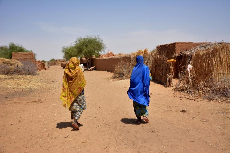 Une matrone marche dans son village avec une femme qu'elle a récemment référée aux équipes de Médecins Sans Frontières.  © Elise Mertens/MSF