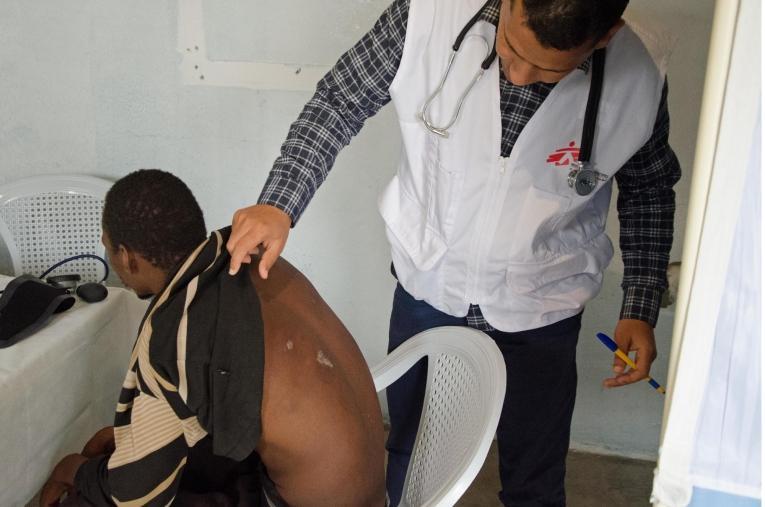 Un médecin MSF ausculte un patient dans une salle de consultation aménagée dans un foyer pour migrants dans la ville de Beni Walid. En collaboration avec une ONG locale, MSF organise des consultations dans ce foyer et des références vers d'autres hôpitaux pour les cas médicaux les plus graves.  © Christophe Biteau/MSF