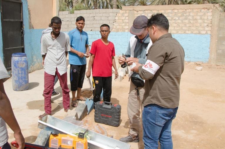 Une équipe de logisticiens MSF dans le centre de détention de Khoms est en train de fixer des lave-mains et échange avec les migrants qui sont détenus. Les conséquences médicales d'un mauvais accès à l'eau potable, telles que les diarrhées, sont parmi les principales pathologies vues en consultation dans les centres de Khoms et Misrata.  © Christophe Biteau/MSF