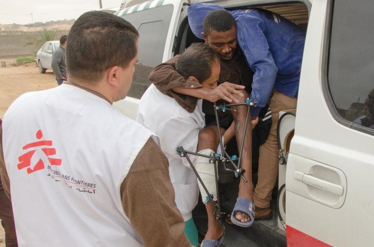 L'équipe médicale MSF réfère un patient depuis Bani Walid vers une structure de soins secondaires. Il est suivi depuis plusieurs semaines et souffre de fractures multiples aux deux jambes. La très grande majorité des patients pris en charge à Bani Walid ont réchappé de prisons clandestines présentes dans la région. Ils ont été kidnappés, torturéset retenus captifs par des réseaux criminels qui leur font vivre un calvaire pour obtenir d'eux une rançon. Ces rescapés sont profondément affaiblis, avec des plaies qui se sont infectées, et de multiples traumatismes.  © Christophe Biteau/MSF