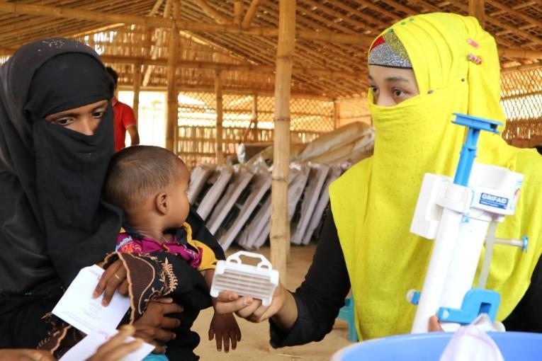Une formatrice locale explique à une ancienne patiente MSF comment utiliser et entretenir un filtre à eau. Ces filtres sont distribués gratuitement par MSF dans le camp deKutupalong-Balukhali.  © MSF
