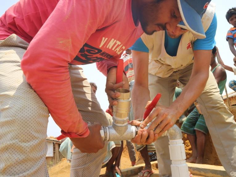 Arafat Hosen (à gauche),superviseur du réseau de distribution d'eau chez MSF, et Thibault Chazal, logisticien MSF, conduisent l'installation d'une pompe à eau submersible dans un puit profond.  © MSF