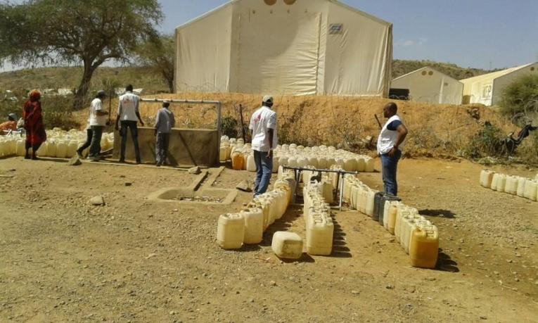 Des habitants du camp de déplacés de Sortonyremplissent des bidons d'eau.  © MSF