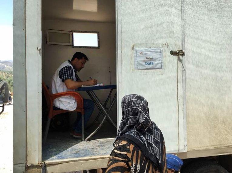 Un responsable des admissions enregistre les informations que lui communique une femme pour sa consultation dans la clinique mobile de MSF.  © Mohammed  Homidan/MSF