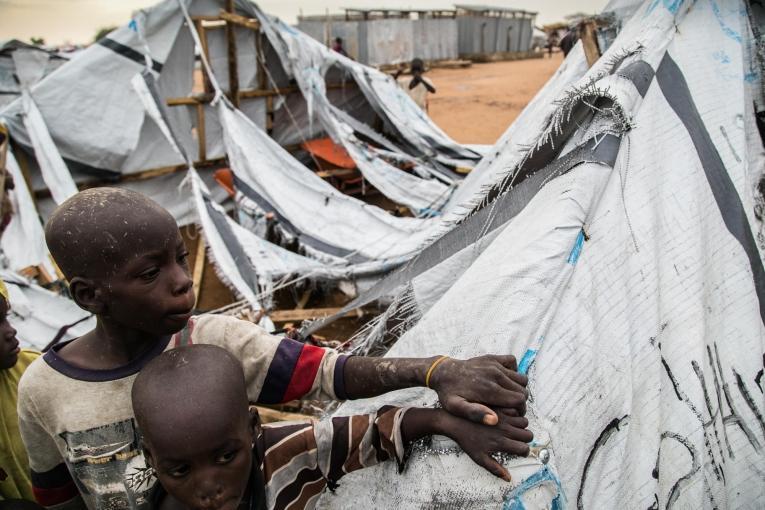 Deux enfants se tiennent devant un abri détruit dans le camp de transit de Pulka.  © Igor G. Barbero/MSF