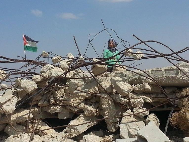 Une jeune femme palestinienne se tient devant les restes de sa maison détruite à Hébron. 2014.  © Muwaffaq Joulani/MSF