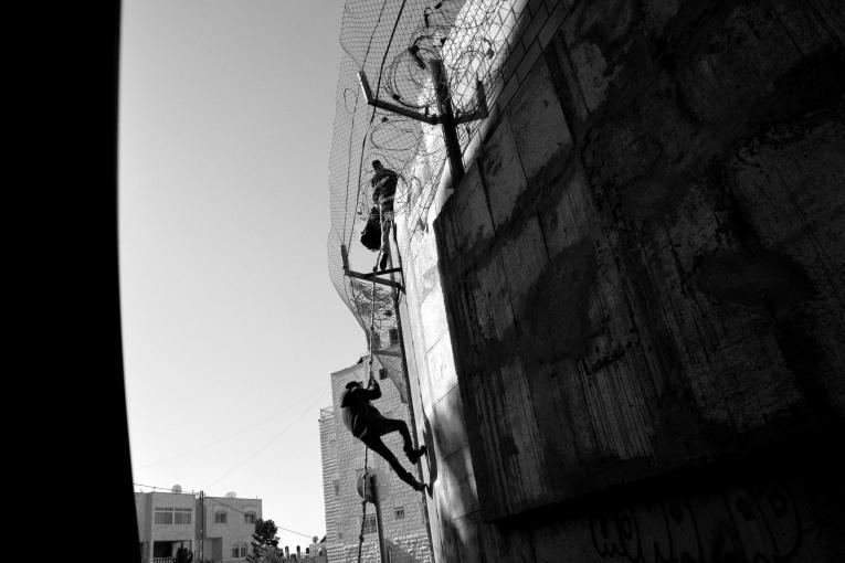 Des palestiniens rentrent à Jérusalem-Est en escaladant le mur pour éviter la longue attente au checkpoint. 2014.   © Aurelie Baumel/MSF