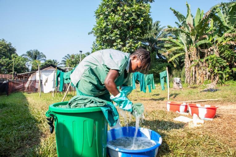 Un membre de l'équipe d'hygiène de MSF lave les blouses désinfectées dans le centre de traitement d'Ebola de MSF à Bikoro, en RDC.  © Louise Annaud/MSF