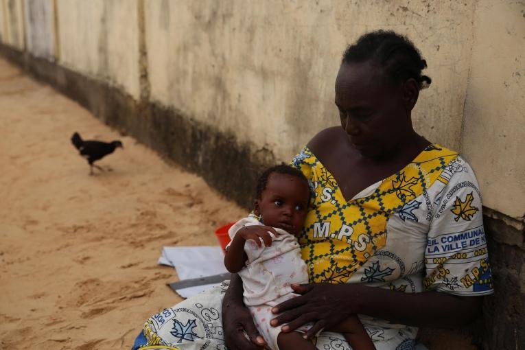 Demba tient son petits-fils dans ses bras. Le garçon de 6 mois commence à aller mieux après 5 jours d'hospitalisation dans le centre nutritionnel thérapeutique de MSF. Tchad. 2018.  © Mohammad Ghannam/MSF