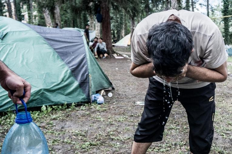 Deux personnes originaires du Kurdistan irakiense lavent les mains avant de cuisiner. Près deBihać, ces personnes ont un accès limité à l'eau. Bosnie-Herzégovine. 2018.  © Kamila Stepien
