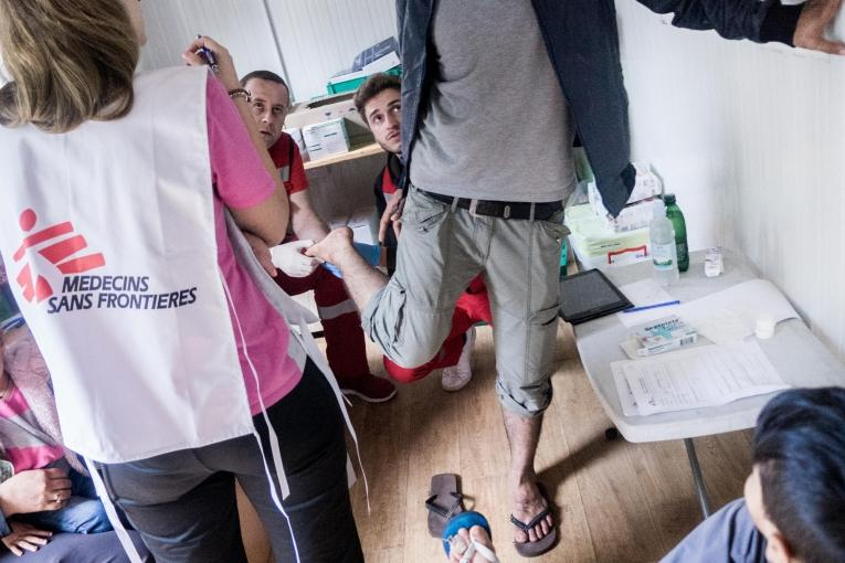 Un jeune Kurde originaire de Syrie lors d'uneconsultation avec les équipes de Médecins Sans Frontières et de la Croix-Rouge bosniaque. Les blessures aux pieds sont fréquentes pour ces personnes qui marchent des jours durant. Bosnie-Herzégovine. 2018.  © Kamila Stepien