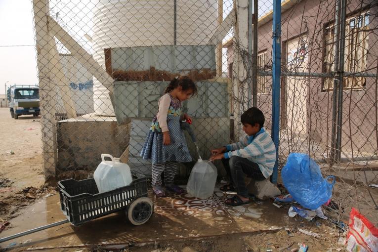 Des enfants remplissent des bidons d'eau dans le camp d'Amriya Falloujah. Irak. 2018.  © Mohammad Ghannam/MSF