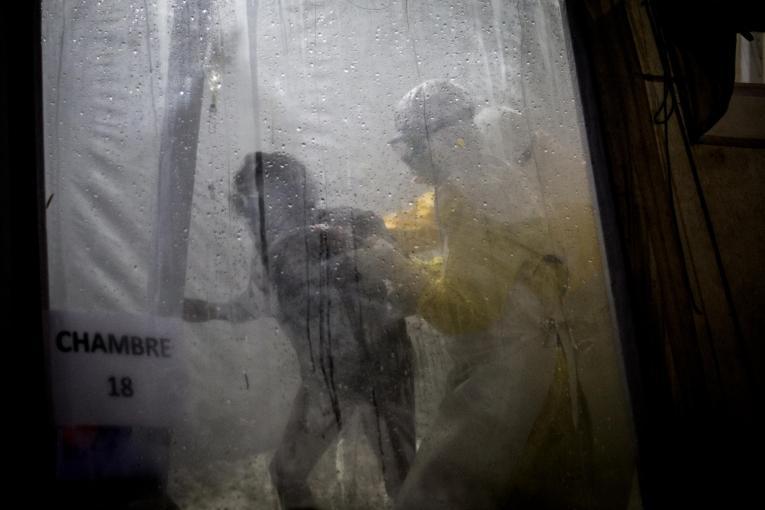 Un travailleur de santé MSF accompagne une patiente Ebola dans son lit du centre de traitement de Butembo. Novembre 2018. République démocratique du Congo.  © John Wessels