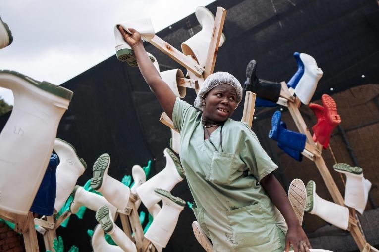 Une travailleuse de santé MSF met à sécher les chaussures désinfectées des équipes du centre de traitement Ebola de Butembo. Novembre 2018. République démocratique du Congo.  © Alexis Huguet