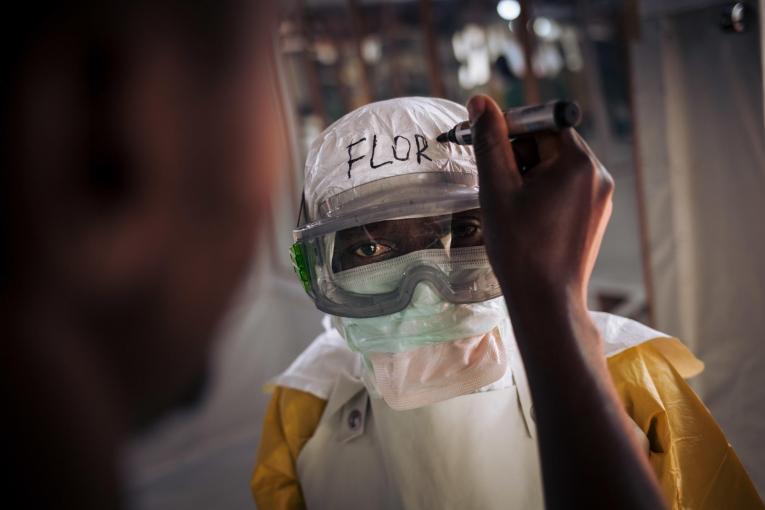 Un travailleur de santé MSF revêt son équipement de protection personnel avant d'entrer dans la zone à risque du centre de traitement Ebola. Leurs noms sont systématiquement écrits sur leur équipement. 2018. République démocratique du Congo.  © Alexis Huguet