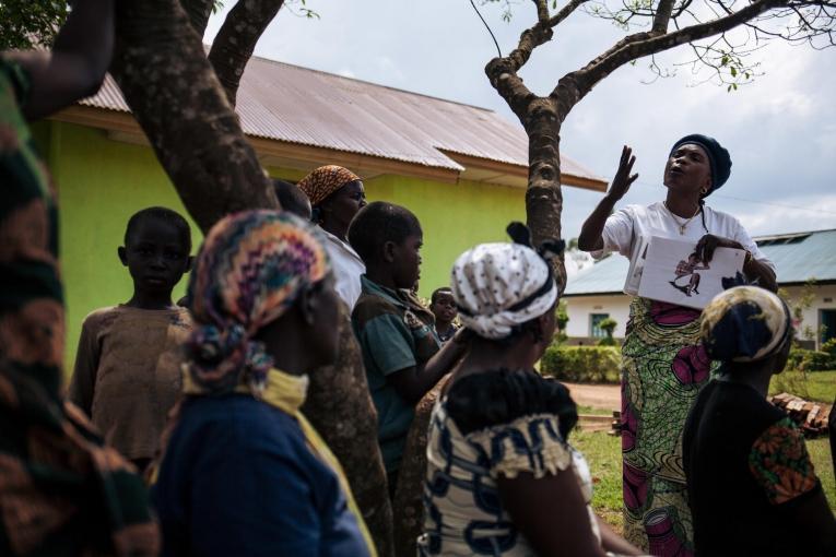 En marge des activités de décontamination d'un hôpital, une travailleuse de santé MSF sensibilise les personnes présentes à l'importance du dépistage Ebola. Novembre 2018. République démocratique du Congo.  © Alexis Huguet