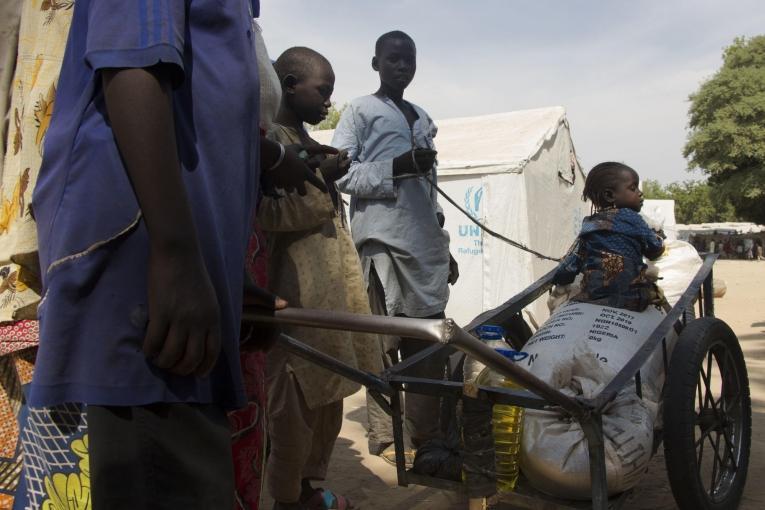 Une petite fille est assisse sur les six mois de rations de nourriture de sa famille après une distribution dans le camp pour personnes déplacées de Bama. Nigeria. 2018.  © Natacha Buhler/MSF