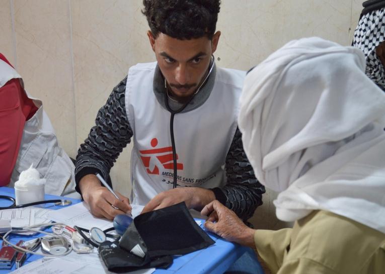 Un infirmier lors d'une consultation avec un patient affecté par une maladie chronique, dans le centre de santé d'Hawija. 2019. Irak.  © MSF