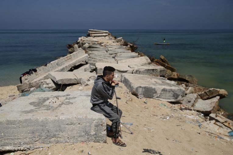 Iyad, 23 ans, est un musicien palestinien blessé par balle par l'armée israélienne le 14 mai 2018. Il est ici assis près de la plage dans la ville de Gaza, en mai 2019.  © Mohammed ABED