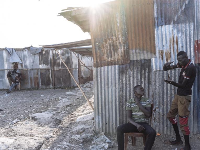 Des barbiers dans la zone du marché du site de protection des civils de Bentiu. 2018. Soudan du Sud.  © Emin Ozmen/Magnum Photos