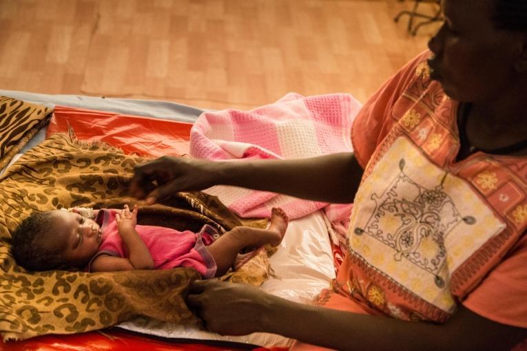 Achol est âgée de 32 ans. Elle est avecTimothy John,son septième enfant, dans l'hôpital MSF du site de protection des civils de Malakal. 2019. Soudan du Sud.  © MSF/Igor Barbero