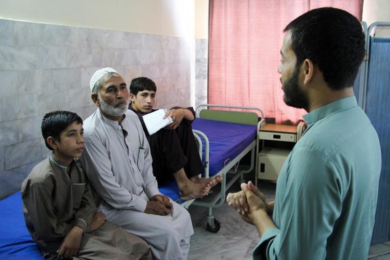 Muhammad Jannat et ses deux fils lors d'une séance de sensibilisation avec un promoteur de santé dans le centre de traitement MSF de Peshawar. 2019. Pakistan.  © Nasir Ghafoor/MSF