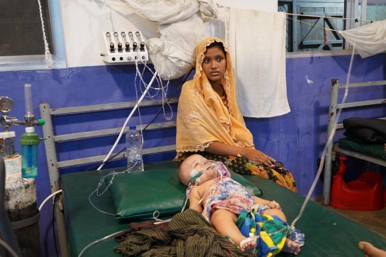 La mère d'un enfant admis dans le centre médical de MSF à Kutupalong estassise sur son lit. Deux ans après les violences d'aout 2017,les réfugiés continuent de vivre dans des conditions précaires. Bien que l'accès à la nourriture, à l'eau et aux soins de base se soit amélioré, il reste insuffisant et inégalement réparti dans les camps.  © Dalila Mahdawi/MSF