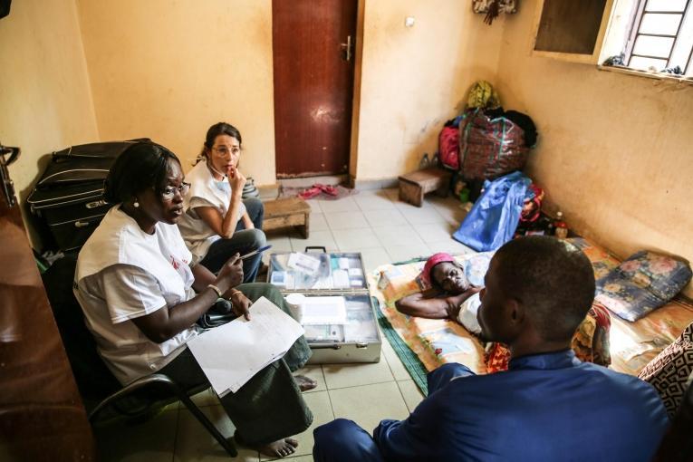 Le Dr. Djénabou Diallo et l'infirmière Nathalie Kornfein en discussion avec une patiente et sa famille à leur domicile. Bamby a 77 ans et elle est atteinte d'un cancer du sein. Les échanges sont importants dans les soins de supports et palliatifs, notamment pour répondre aux nombreuses questions concernant l'état du patient. Mali. 2019.  © MSF/Mohammad Ghannam