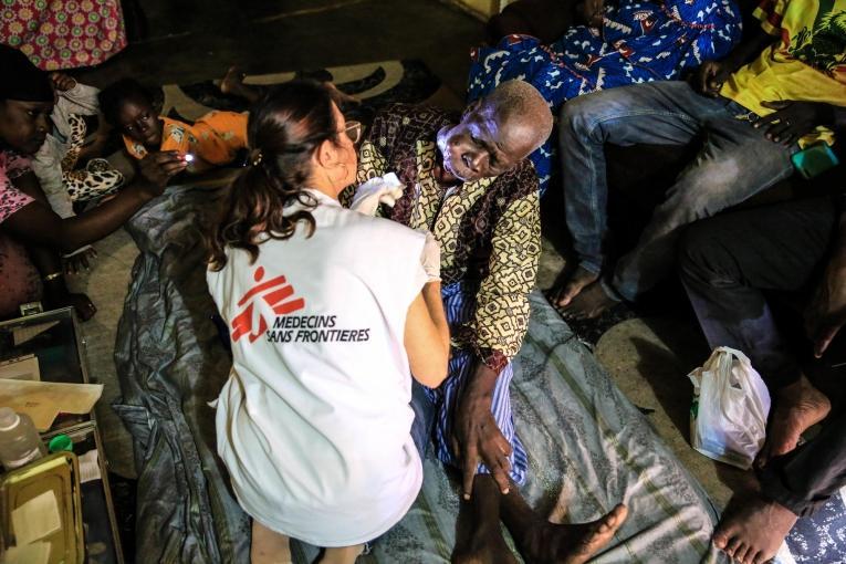 L'infirmière Nathalie Kornfein change le pansement de Maady Dabo, un patient âgé de 76 ansatteint d'un cancer oral. Pendant les soins, il est entouré par sa famille. Mali. 2019.  © MSF/Mohammad Ghannam