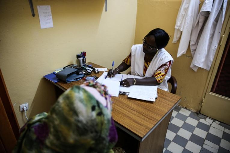 Le Dr. Djénabou Diallo prescrit des médicaments à une patiente âgée de 36 ans, atteinte d'un cancer du sein, dans le service d'hémato-oncologie hôpital du Point G. Les médicaments prescrits sont fournis gratuitement par MSF et comprennent notamment des puissants antidouleurs et des antibiotiques. Mali. 2019.  © MSF/Mohammad Ghannam