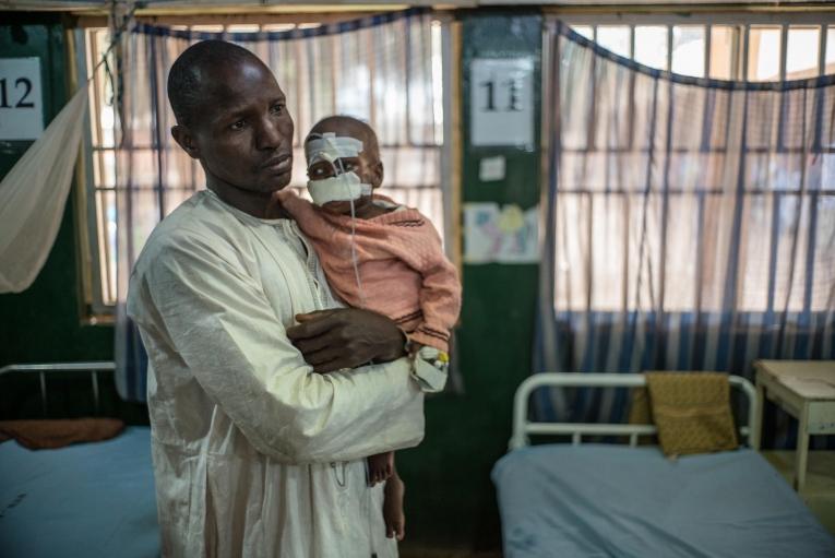 Un père et son fils à l'hôpital de Sokoto. Le petit garçon de deux ans souffrait de malnutrition due à sa difficulté à ingérer les aliments. Le noma a détruit une partie de son visage. Nigeria. 2016.    © Claire Jeantet - Fabrice Caterini/Inediz
