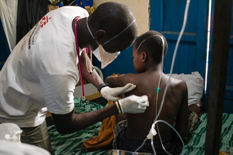Le Dr. Birame, en charge des activités médicales à l'hôpital général de référence de la région de Nizi, effectue une ponction dans le poumon gauche d'un jeune patient de 14 ans après une infection pulmonaire. Après seulement 48 heures, grâce au traitement et aux piqûres, le patient respire mieux et n'a plus de fièvre.  © MSF/Solen Mourlon
