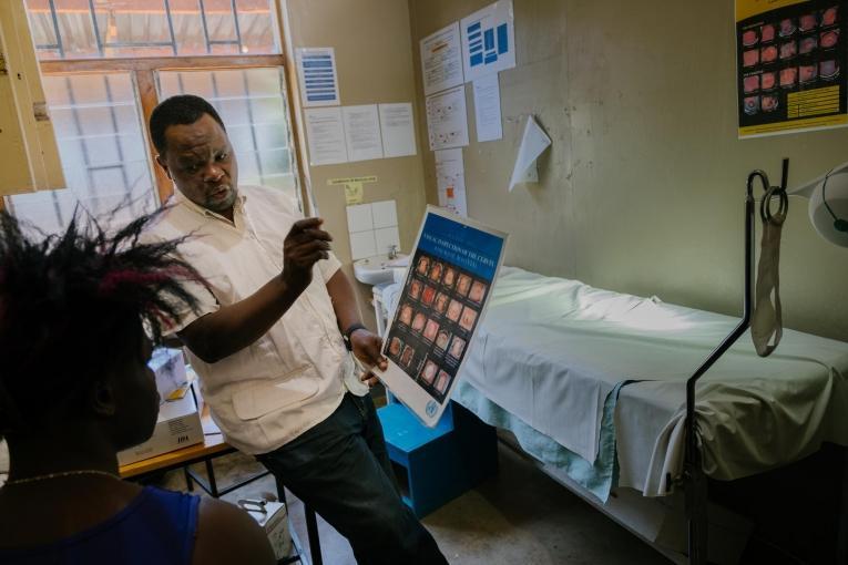 Prince Nkhoma explique le processus de dépistage du cancer du col de l'utérus à une jeune femme de 22 ans dans un dispensaire MSF pour les professionnel.le.s du sexe, intégré à l'hôpital de district de Mwanza. Le risque de développer un cancer du col de l'utérus est particulièrement élevé chez les professionnel.le.s du sexe : une mauvaise utilisation du préservatif et de multiples partenaires sexuels entraînent une transmission plus élevée du virus HP (HPV), qui provoque le cancer du col. Malawi.  © Isabel Corthier