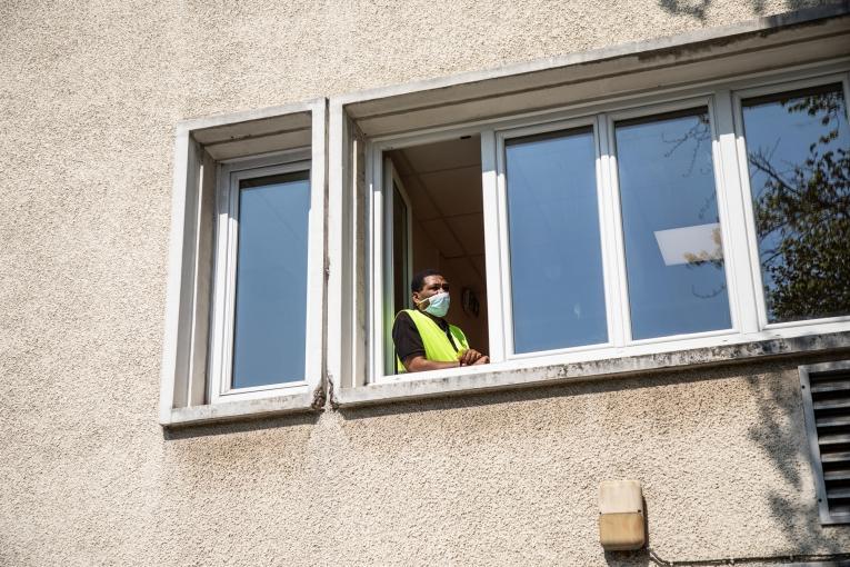 L'un des agents de sécurité du centre, à la fenêtre du premier étage. Paris, avril 2020.  © Agnes Varraine-Leca/MSF