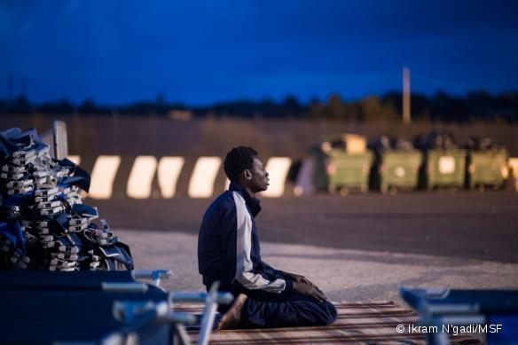 Un jeune homme en provenance de Gambie prie dans le camp de transit de Augusta en Italie, quelqeus heures après avoir été repêché en mer. Septembre 2014.