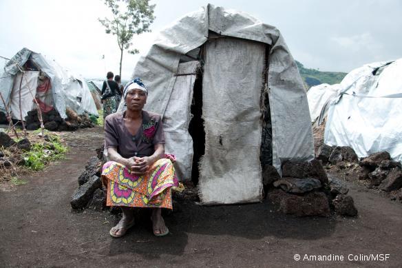 Comme Victorine, cette femme déplacée se tient devant son abri, dans le camp de Bulengo