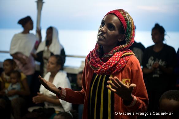 Une femme érythréenne chante une prière avec d'autres femmes et enfants après avoir été secourue le 2 septembre 2015 en mer Méditerranée par le MY Phoenix, bateau de recherche et de sauvetage de MSF.