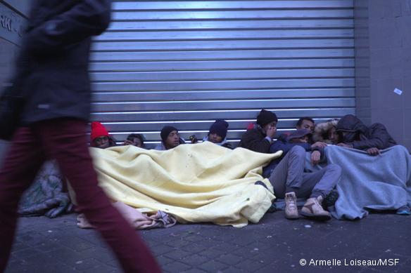 Des migrants blottis sous des couvertures près de la Halle Pajol, dans le 18ème arrondissement de Paris, le 10 janvier 2017.