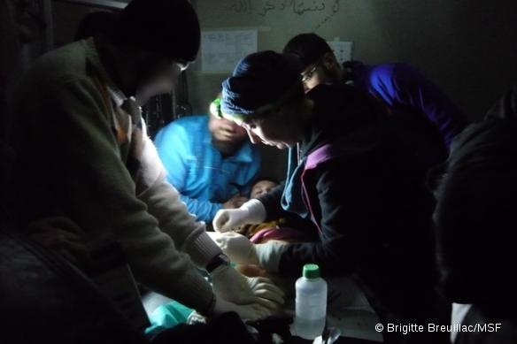 Un médecin de MSF soigne un garçon grièvement brûlé dans un poste médical avancé, en Syrie.